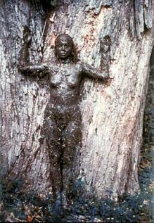 Tree of Life by Ana Mendieta, 1976 - photograph of Mendieta covered in mud, leaning up against, and somewhat blending in with, a large tree.